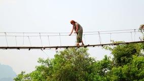 Mujer turística que cruza puente colgante de bambú peligroso, Laos almacen de metraje de vídeo