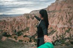 Mujer turística que detiene al hombre a mano y que camina abajo del camino cerca en el valle de la montaña Fotos de archivo libres de regalías