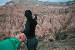 Mujer turística que detiene al hombre a mano y que camina abajo del camino cerca en el valle de la montaña Foto de archivo