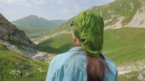 Mujer turística que mira en paisaje verde del valle de la montaña mientras que el caminar del verano metrajes