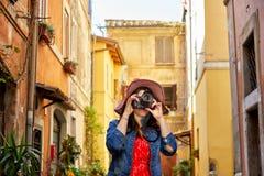 Mujer turística que se coloca y que se enfoca con la cámara Fotos de archivo libres de regalías