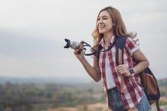 Mujer turística que toma la foto con su cámara en naturaleza foto de archivo
