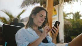 Mujer turística relajada feliz que hace compras en línea usando el app del smartphone que sonríe, descansando en silla exótica de almacen de metraje de vídeo