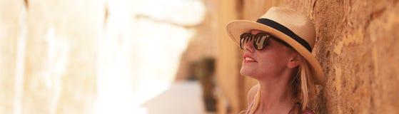 Mujer turística rubia en el sombrero que presenta en la bandera de pared vieja imagen de archivo