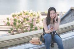 Mujer turística a solas asiática hermosa que relaja y que disfruta de escuchar la música en un smartphone en centro de la ciudad  foto de archivo libre de regalías