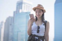 Mujer turística a solas asiática hermosa que sonríe y que mira el teléfono móvil para buscar el punto de visita turístico de excu fotografía de archivo libre de regalías
