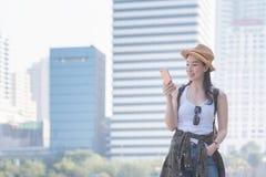 Mujer turística a solas asiática hermosa que sonríe y que mira el teléfono móvil para buscar el punto de visita turístico de excu fotos de archivo libres de regalías