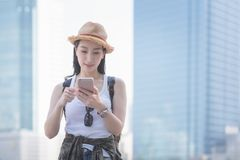 Mujer turística a solas asiática hermosa que sonríe y que mira el teléfono móvil para buscar el punto de visita turístico de excu imagen de archivo