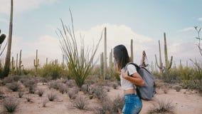 Mujer turística sonriente feliz joven de la cámara lenta con la mochila que explora el desierto atmosférico del cactus en el parq metrajes