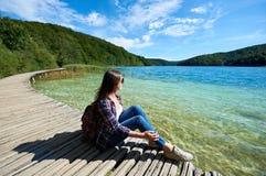 Mujer turística sonriente joven en gafas de sol y con la mochila que se sienta en el puente de madera foto de archivo libre de regalías