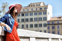 Mujer turística sonriente que mira lejos en la calle soleada de la ciudad Fotos de archivo libres de regalías