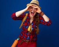 Mujer turística sonriente que mira a través de las manos formadas binoculares Fotografía de archivo