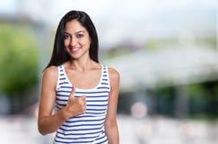 Mujer turca hermosa en una camisa del verano que muestra el pulgar para arriba Imagen de archivo