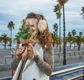 Mujer turística en Barcelona que oculta detrás de un pequeño árbol de navidad Imagenes de archivo