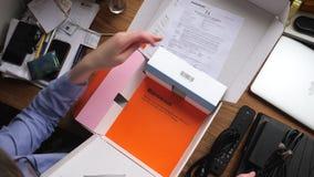 Mujer unboxing el nuevo receptor de la sistema-caja de la TV de telecomunicaciones anaranjadas almacen de metraje de vídeo