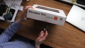 Mujer unboxing el nuevo receptor de la sistema-caja de la TV de telecomunicaciones anaranjadas almacen de video
