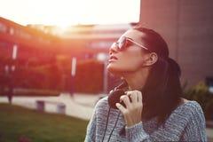 Mujer urbana de moda elegante que disfruta de puesta del sol en gafas de sol Foto de archivo