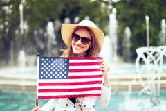 Mujer urbana del patriota joven que estira la bandera de los E.E.U.U. en parque imágenes de archivo libres de regalías
