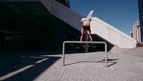 Mujer urbana que hace una posición del pino almacen de metraje de vídeo