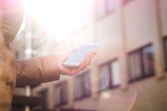 Mujer urbana que sostiene smartphone y que camina en sol Forma de vida moderna y de moda Salida del sol o puesta del sol en el ce Foto de archivo