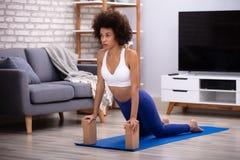 Mujer usando bloques de madera mientras que hace ejercicio foto de archivo