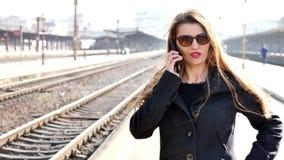 Mujer usando el tel?fono en la estaci?n de tren almacen de video
