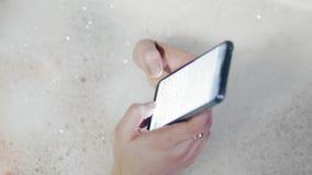 Mujer usando Smartphone mientras que teniendo baño, ciérrese para arriba