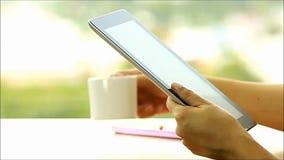 Mujer usando Tablet PC y café de consumición en casa por la mañana almacen de video