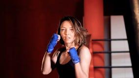 Mujer valerosa que indica con su mano en estudio del boxeo metrajes