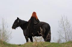 Mujer valiente con el pelo rojo en capa negra en el caballo frisio Foto de archivo libre de regalías
