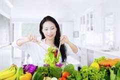 Mujer vegetariana que revuelve la ensalada Fotografía de archivo libre de regalías