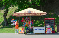 Mujer-vendedor en parque en el contador con el helado, globos Fotos de archivo