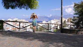 Mujer venida al punto de visión para admirar el paisaje urbano de Agios Nikolaos, Creta metrajes
