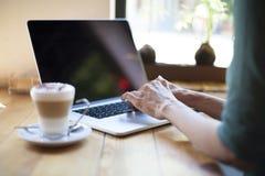Mujer verde de la camisa que mecanografía el ordenador portátil de la pantalla en blanco Imagen de archivo libre de regalías