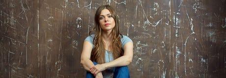 Mujer vestida casual con el pelo largo que se sienta en un piso Fotografía de archivo libre de regalías
