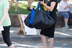 Mujer vestida en el vestido negro que sostiene muchos bolsos imagen de archivo libre de regalías