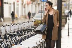 Mujer vestida invierno cerca de la bicicleta Fotografía de archivo libre de regalías