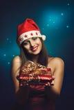 Mujer vestida la Navidad que ofrece un regalo foto de archivo