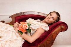 Mujer victoriana con las flores en el sofá de desfallecimiento fotografía de archivo libre de regalías