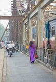 Mujer vietnamita en el vestido tradicional Ao Dai que camina en el puente largo viejo de Bien, ciudad de Hanoi fotos de archivo
