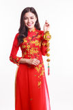 Mujer vietnamita hermosa con ao rojo dai que sostiene el ornamento afortunado del Año Nuevo Imagen de archivo libre de regalías