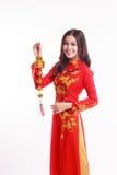 Mujer vietnamita hermosa con ao rojo dai que sostiene el ornamento afortunado del Año Nuevo Fotos de archivo libres de regalías