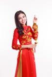 Mujer vietnamita hermosa con ao rojo dai que sostiene el ornamento afortunado del Año Nuevo Foto de archivo
