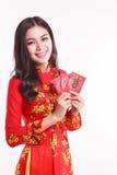 Mujer vietnamita hermosa con ao rojo dai que sostiene el paquete rojo Fotos de archivo libres de regalías