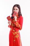Mujer vietnamita hermosa con ao rojo dai que sostiene el paquete rojo Imágenes de archivo libres de regalías