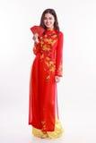 Mujer vietnamita hermosa con ao rojo dai que sostiene el paquete rojo Imagen de archivo libre de regalías
