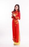 Mujer vietnamita hermosa con ao rojo dai que sostiene el paquete rojo Fotografía de archivo libre de regalías