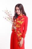Mujer vietnamita hermosa con ao rojo dai que sostiene la flor de cerezo Foto de archivo