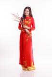 Mujer vietnamita hermosa con ao rojo dai que sostiene la flor de cerezo Foto de archivo libre de regalías