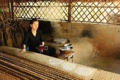 Mujer vietnamita que cocina el papel de arroz tradicional a mano fotografía de archivo libre de regalías